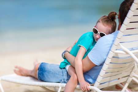 Happy father and his adorable little daughter at tropical beach during summer vacation photo