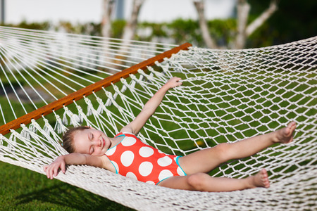aviators: Adorable little girl on summer vacation relaxing in hammock Stock Photo