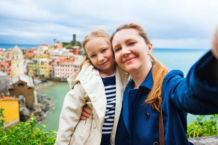 Mother and daughter taking selfie with smartphone having scenic view of colorful village Vernazza, Cinque Terre, Italy on background photo