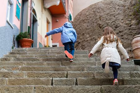 upstairs: Kids running upstairs at street of colorful Manarola village, Cinque Terre, Italy