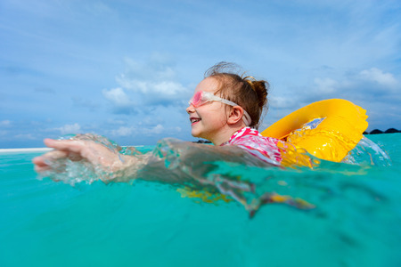 girl with rings: Adorable little girl with yellow inflatable ring swimming in a tropical ocean on summer vacation