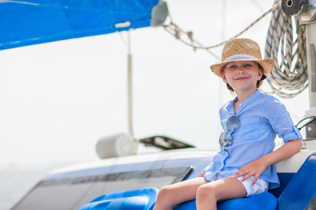 Adorable little girl enjoying sailing on a luxury catamaran or yacht photo