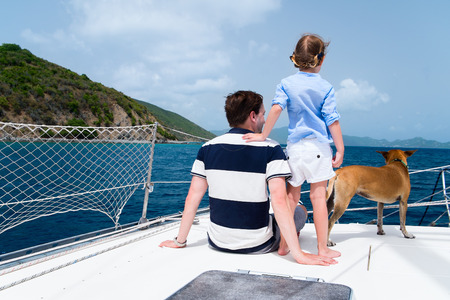 boating: Father, daughter and their pet dog sailing on a luxury yacht or catamaran boat