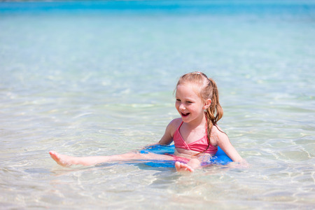 Little girl on vacation swimming in a shallow water at tropical ocean Stock Photo