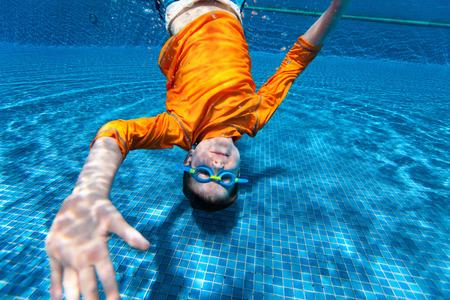 underwater sport: Cute boy underwater in swimming pool