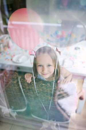 children birthday: Adorable little girl with colorful balloons at kids birthday party looking through a window