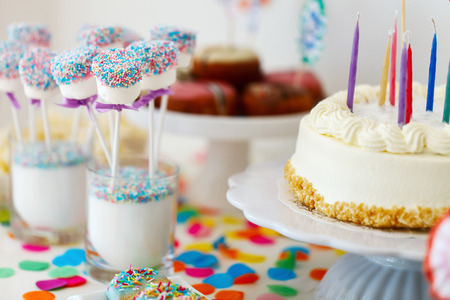 party food: Cake, candies, marshmallows, cakepops, fruits and other sweets on dessert table at kids birthday party Stock Photo