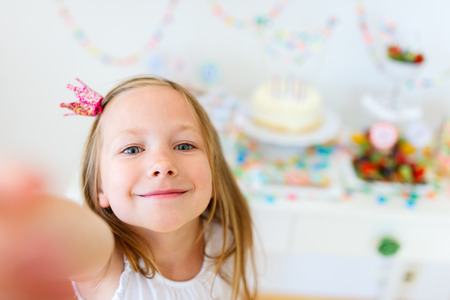 Bedårande liten flicka med prinsesskrona på barn födelsedagsfest gör selfie