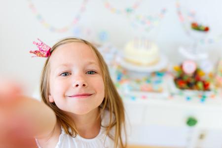 Schattig meisje met prinses kroon op kids verjaardagsfeestje making selfie Stockfoto