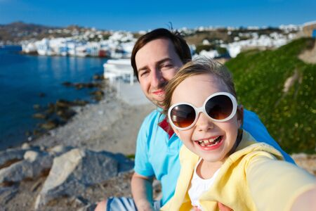 little venice: Happy family father and his adorable little daughter on vacation taking selfie at Little Venice area on Mykonos island, Greece