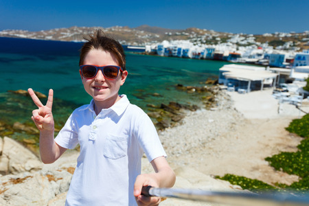 little venice: Cute teenage tourist making selfie with a stick at place overlooking Little Venice area on Mykonos island, Greece