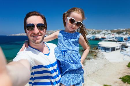Gelukkig gezin vader en zijn schattige dochtertje op vakantie nemen selfie bij Little Venice gebied op het eiland Mykonos, Griekenland
