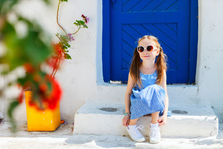 greece: Charming little girl at typical greek traditional village with white houses and colorful doors on Mykonos Island, Greece, Europe