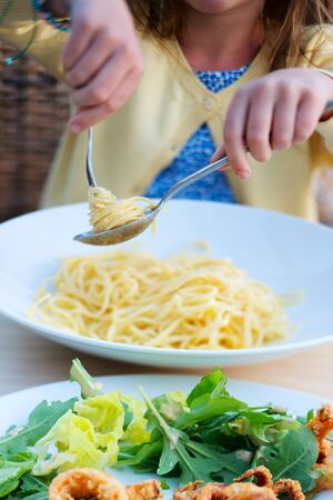 unrecognisable person: Close up of adorable little girl eating spaghetti for a lunch at restaurant Stock Photo