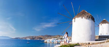 White greek windmills overlooking Little Venice popular tourist destination at traditional village on Mykonos Island, Greece, Europe photo