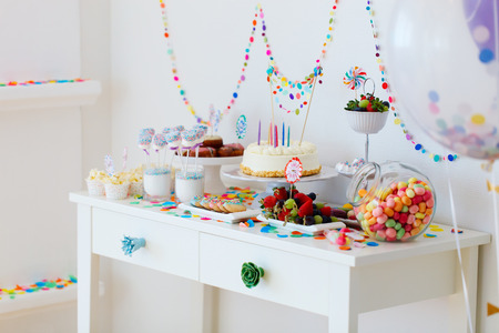 Cake, candies, marshmallows, cakepops, fruits and other sweets on dessert table at kids birthday party Imagens