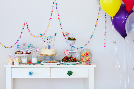 party table: Cake, candies, marshmallows, cakepops, fruits and other sweets on dessert table at kids birthday party Stock Photo