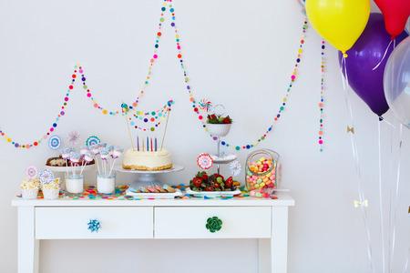 postres: La torta, dulces, bombones, cakepops, frutas y otros dulces en la mesa de postres en la fiesta de cumpleaños de los niños