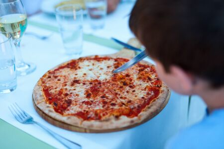 unrecognisable person: Back view of boy eating pizza for lunch Stock Photo