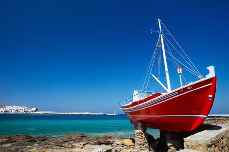 boat fishing: Red boat on island of Mykonos, Greece Stock Photo