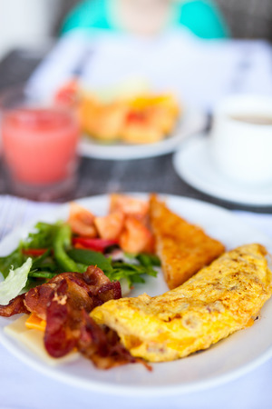 Delicious breakfast with omelet, bacon and vegetables photo