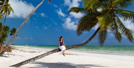 Young beautiful woman sitting on palm tree relaxing at white sand tropical beach