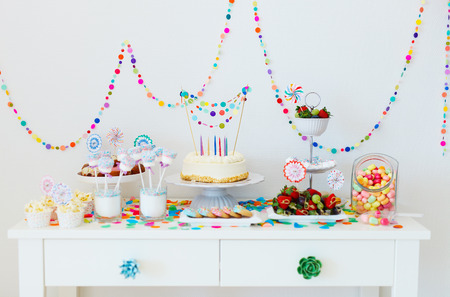 dessert stand: Cake, candies, marshmallows, cakepops, fruits and other sweets on dessert table at kids birthday party Stock Photo