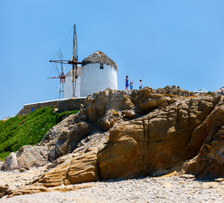 Family of mother and kids in front of windmills at popular tourist area on Mykonos island, Greece photo