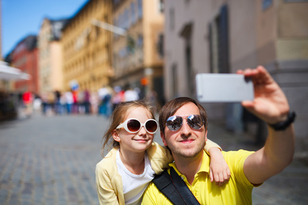 europe travel: Happy family father and his adorable little daughter taking selfie with mobile phone outdoors at street of Stockholm, Europe