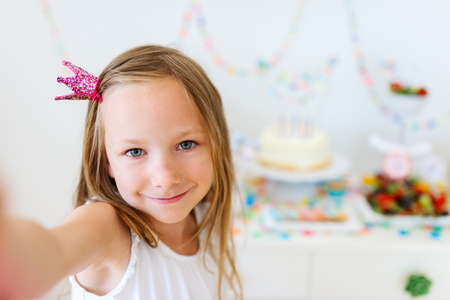 children birthday: Adorable little girl with princess crown at kids birthday party taking selfie