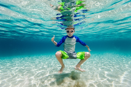 underwater sport: Cute teenage boy swimming underwater in shallow turquoise water at tropical beach