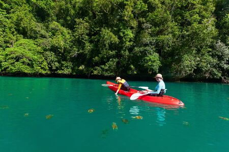 mangrove: Family of mother and son paddling on kayak in ocean among jellyfish during summer vacation