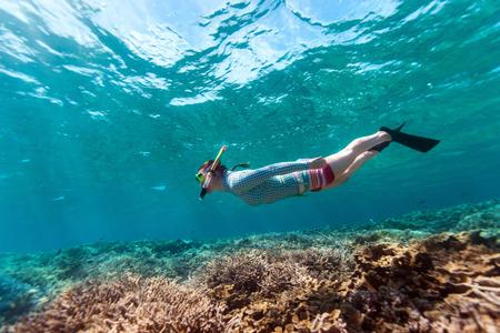 산호초에서 분명 열 대 물에서 여자 스노클링과 프리 다이빙의 수중 사진