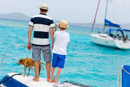 boat: Father, son and their pet dog sailing on a luxury yacht or catamaran boat Stock Photo