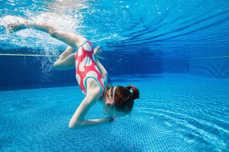 petite fille maillot de bain: Photo sous-marine de petite fille adorable plongée et la natation dans la piscine en vacances d'été Banque d'images