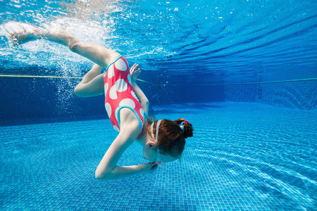 children swimsuit: Underwater photo of adorable little girl diving and swimming in pool on summer vacation Stock Photo