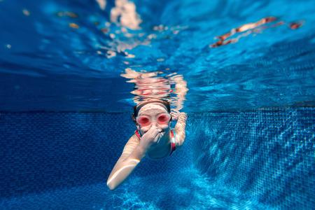 picada: Fotografía submarina de buceo poco adorable niña y nadar en la piscina en vacaciones de verano Foto de archivo