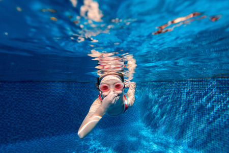diving: Underwater photo of adorable little girl diving and swimming in pool on summer vacation Stock Photo