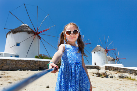 sticks: Cute little girl taking selfie with a stick in front of windmills at popular tourist area on Mykonos island, Greece