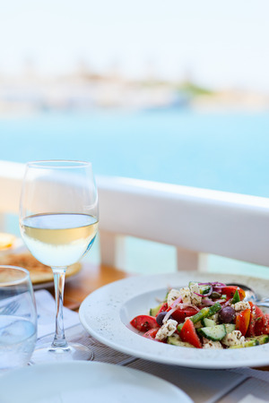 food and wine: Delicious fresh greek salad and glass of white wine served for lunch at outdoor restaurant Stock Photo