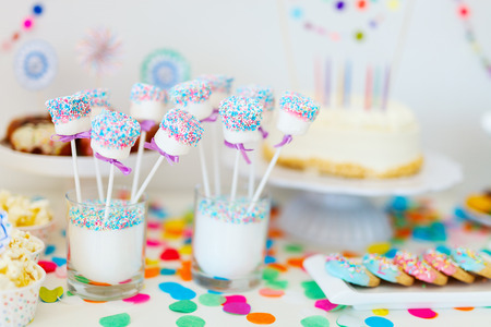 Cake, candies, marshmallows, cakepops, fruits and other sweets on dessert table at kids birthday party Banque d'images