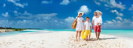 家人: 幸福美滿的家庭與孩子們在暑假期間對熱帶海灘走在一起全景 版權商用圖片