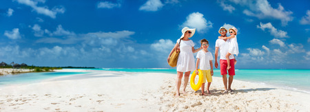 Panorama of happy beautiful family with kids walking together on tropical beach during summer vacation. Stock Photo