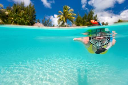 Kvinna snorkling i klart tropiska vatten framför exotiska ön