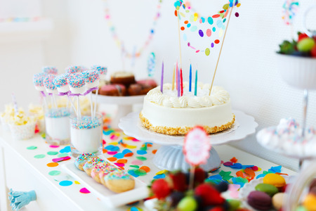 birthday celebration: Cake, candies, marshmallows, cakepops, fruits and other sweets on dessert table at kids birthday party Stock Photo