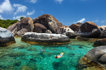 Family of mother and son snorkeling in turquoise tropical water among huge granite boulders at The Baths beach area major tourist attraction on Virgin Gorda, British Virgin Islands, Caribbean Stock Photo