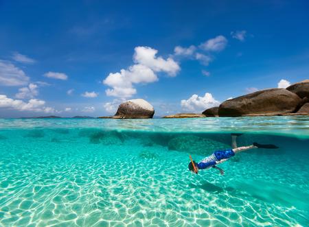 Split foto av liten pojke snorkling i turkost hav vatten vid tropiska ön Virgin Gorda, Brittiska Jungfruöarna, Karibien