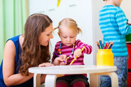 젊은 어머니와 함께 드로잉하는 그녀의 딸. 또한 유치원 보육 환경에 적합합니다.