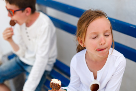 Two adorable kids eating ice cream outdoors on a hot summer day Stock Photo