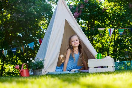 Schattig klein meisje met plezier spelen buiten op zomerdag Stockfoto